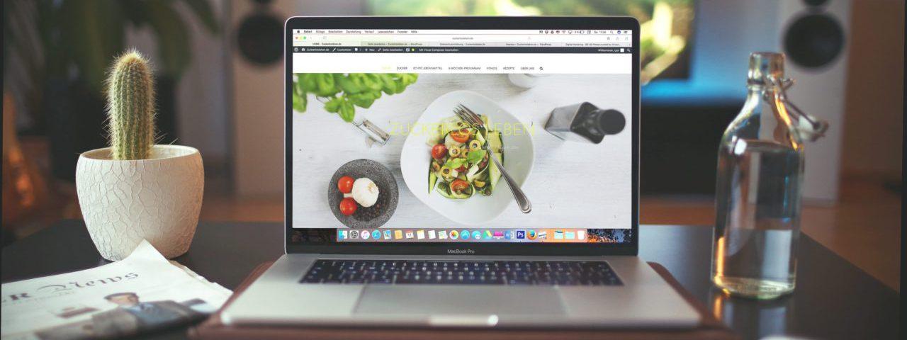 Tafel met een laptop, fles water en plant