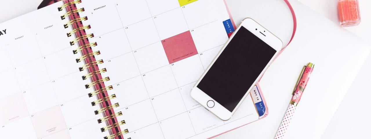 Bovenaanzicht van een agenda, smartphone en balpen