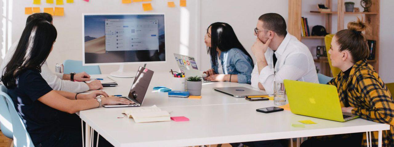 Vijf mensen die samen een website over leggen op groot scherm